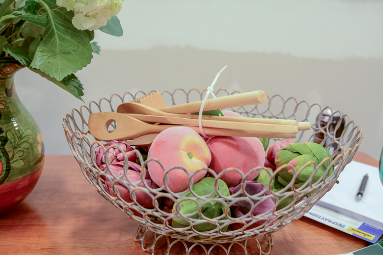 wire bowl with peaches, artichokes and wooden spoons in it