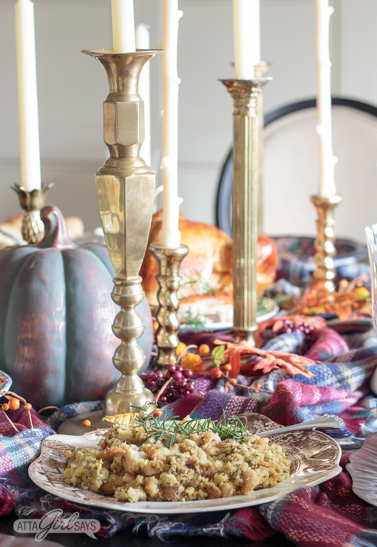 Thanksgiving table set with brass candlesticks, pumpkins and plaid table scarft