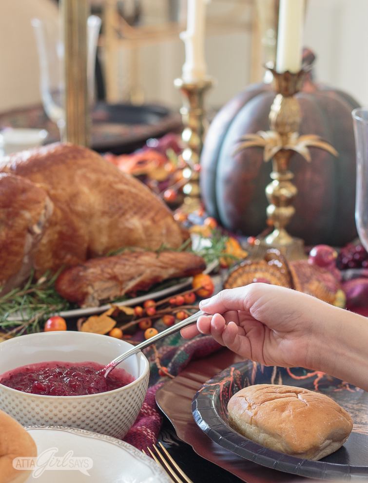 child serving cranberry sauce onto his plate at Thanksgiving