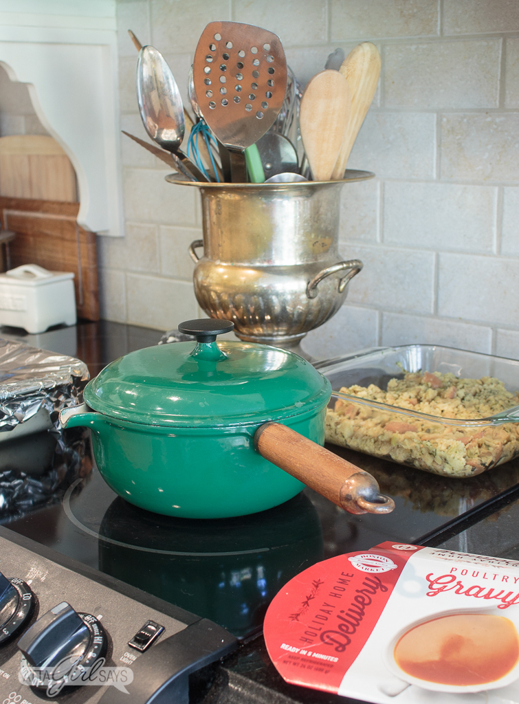 green pot and pyrex baking dishes filled with Thanksgiving side dishes on top of a stove for an easy Thanksgiving dinner
