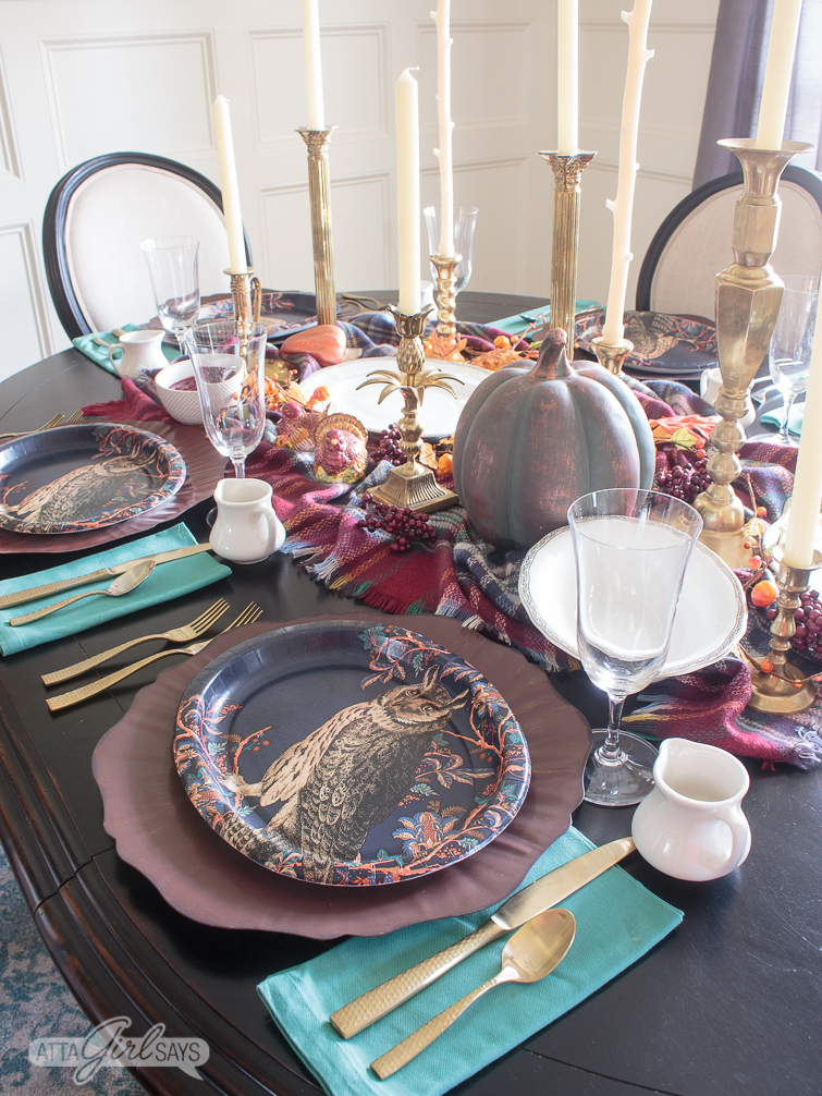 overhead view of a dining table set for Thanksgiving with blue paper owl plates on copper chargers, a plaid tables scarf, pumpkins and brass candlesticks