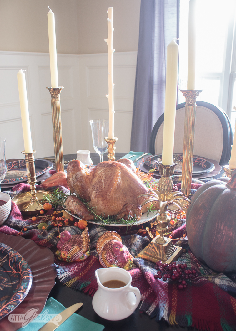 Thanksgiving turkey on a table set with brass candlesticks, pumpkins and a plaid blanket scarf