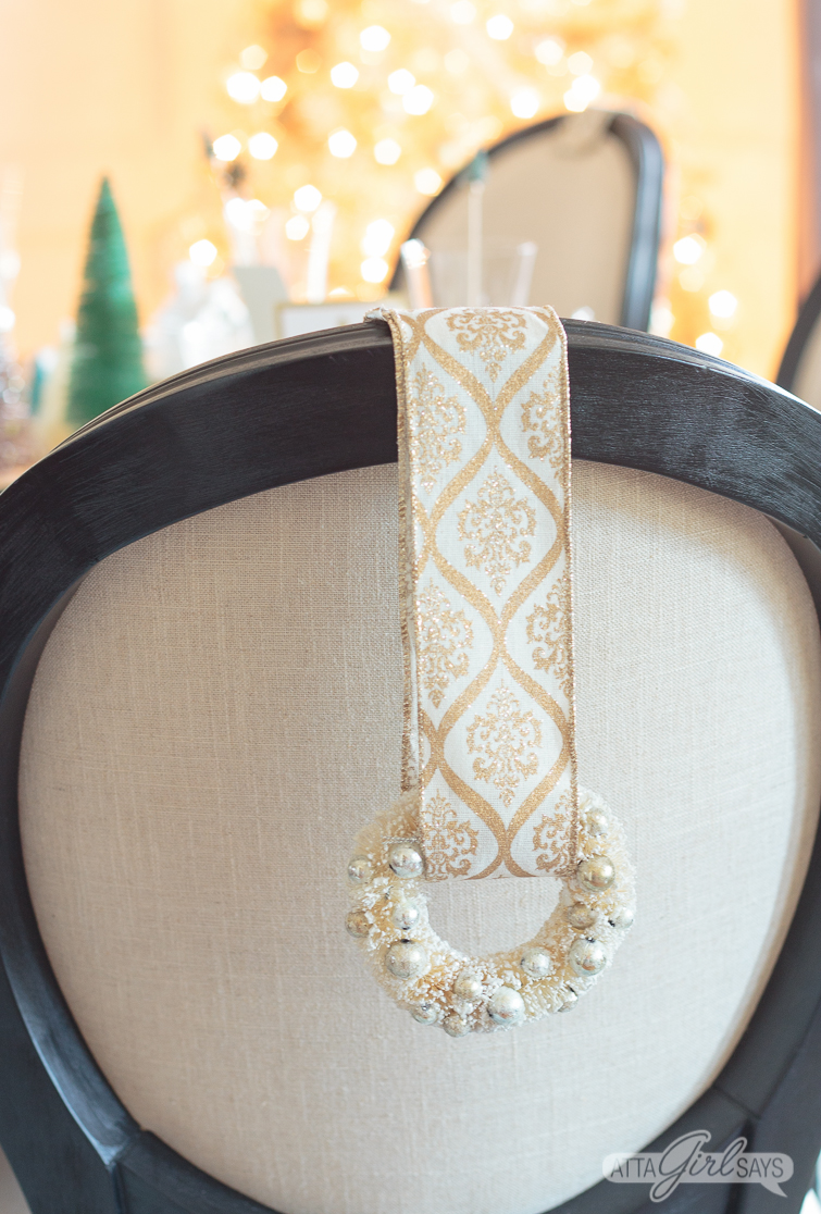 gold and white bottlebrush wreath hanging from the back of a black upholstered dining room chair