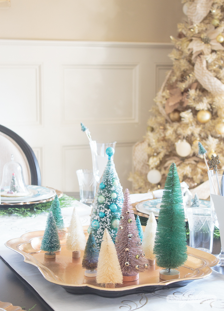 aqua and white bottlebrush Christmas trees on a gold tray on a dining room table with a gold Christmas tree in the background