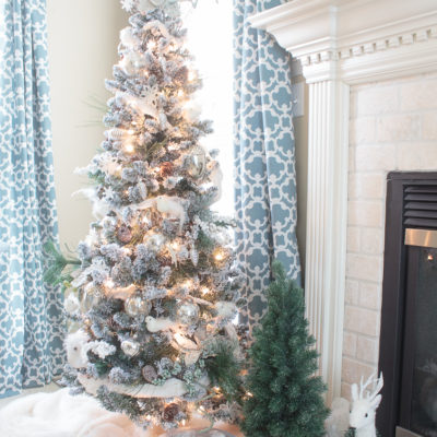 fireplace hearth with two Christmas trees, birch logs and a snowy white deer decoration