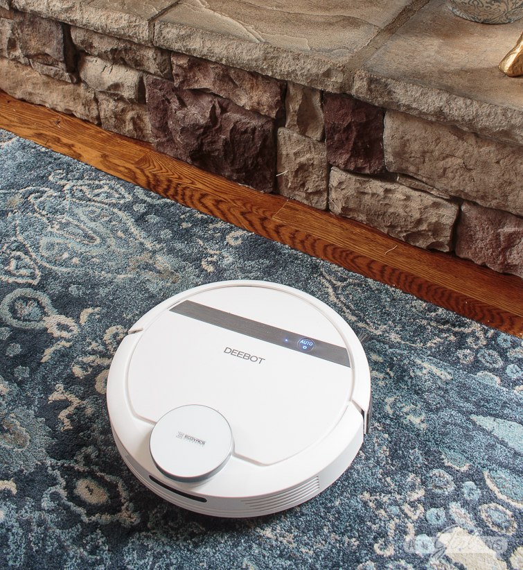 ECOVACS DEEBOT vacuum on a blue and gray rug