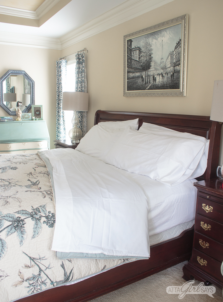 king size sleigh bed with white sheets and a blue bird comforter