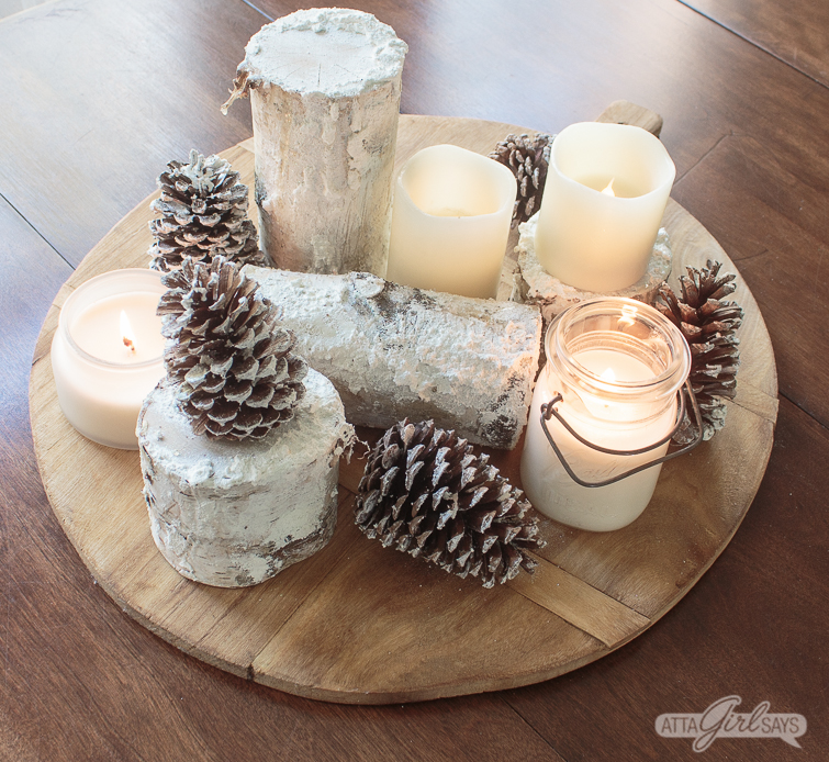 winter centerpiece created using snowy birch logs, pinecones, candles on a bread board