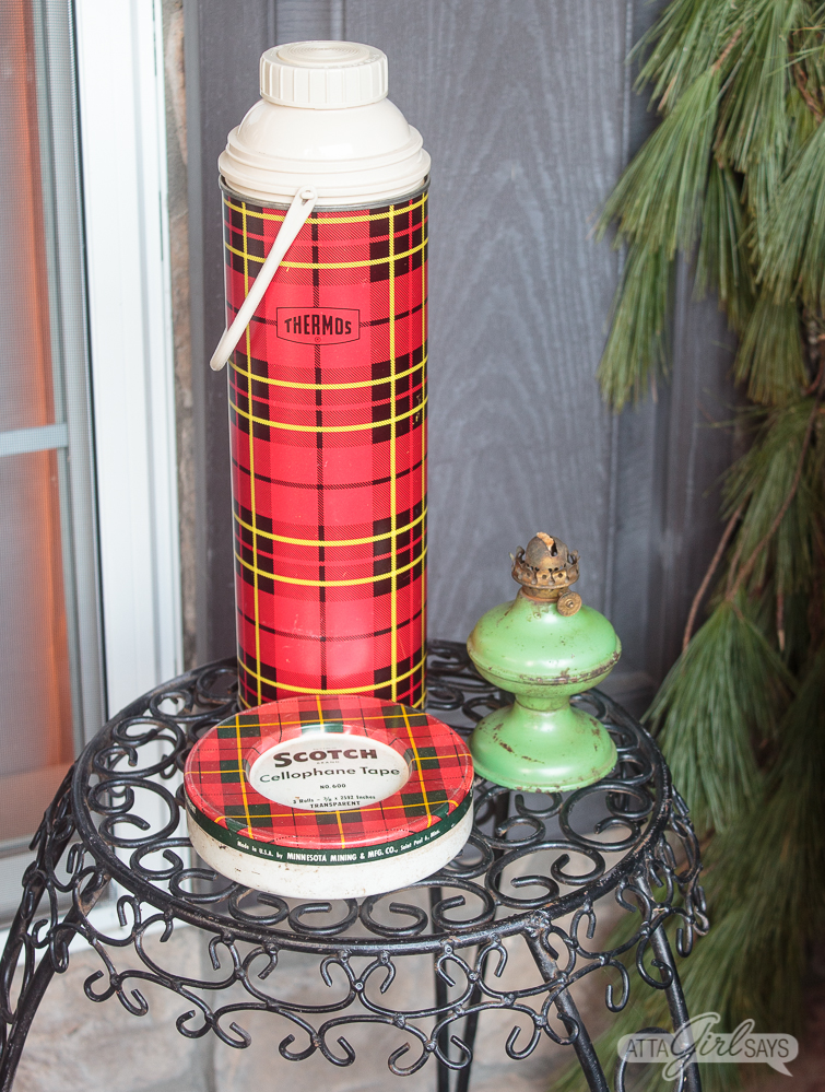 plaid Thermos, tin Scotch tape canister and green oil lamp on a wrought iron table
