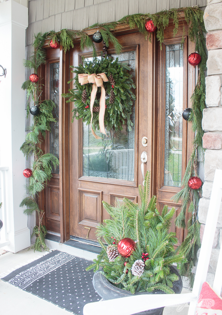 front door decorated with an evergreen wreath, garlands and black urns for Christmas