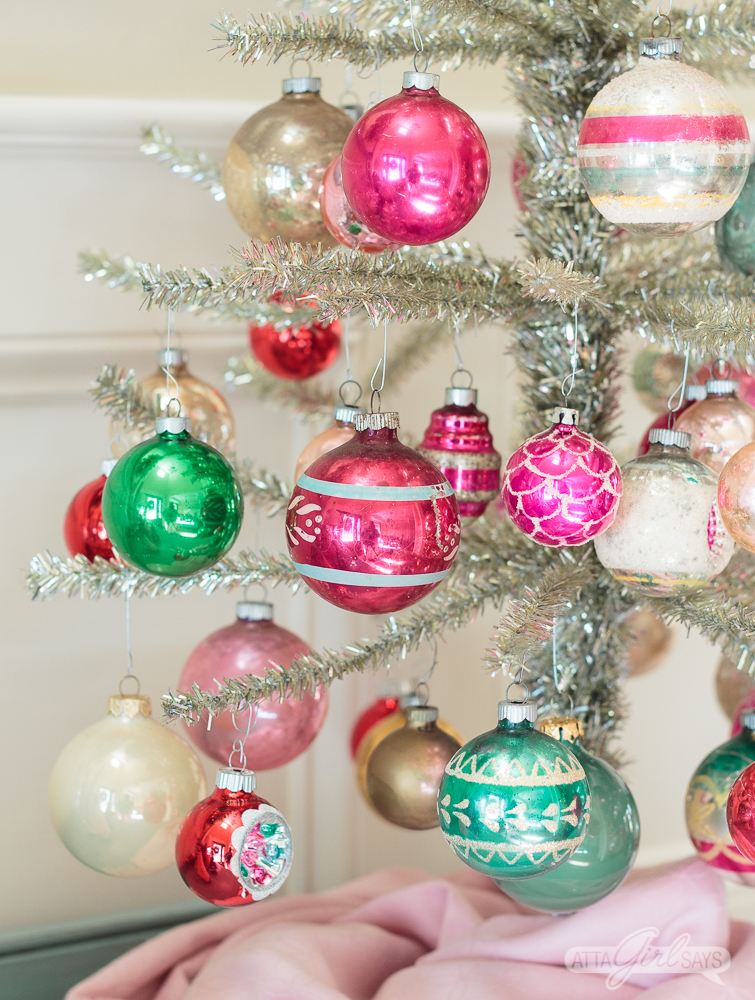feather tinsel Christmas tree decorated with pink and green Shiny Brite ornaments on top of an aqua buffet