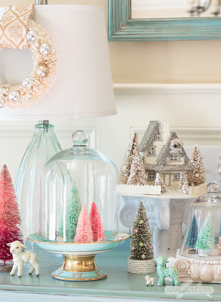 colorful bottle brush Christmas trees in pastel colors on top of an aqua painted buffet