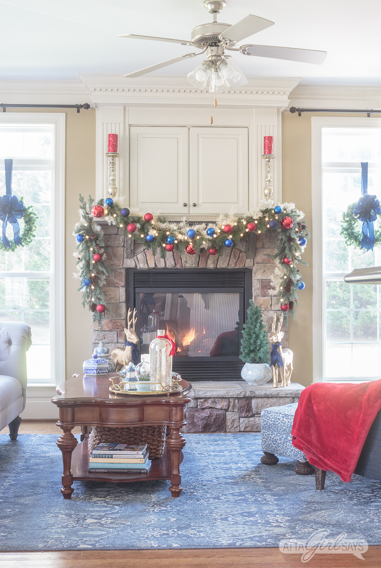 stone fireplace hearth and mantel decorated for Christmas with a red and blue garland