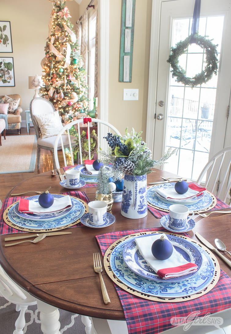 Breakfast table set with blue and white dishes for Christmas with a Christmas tree in the background