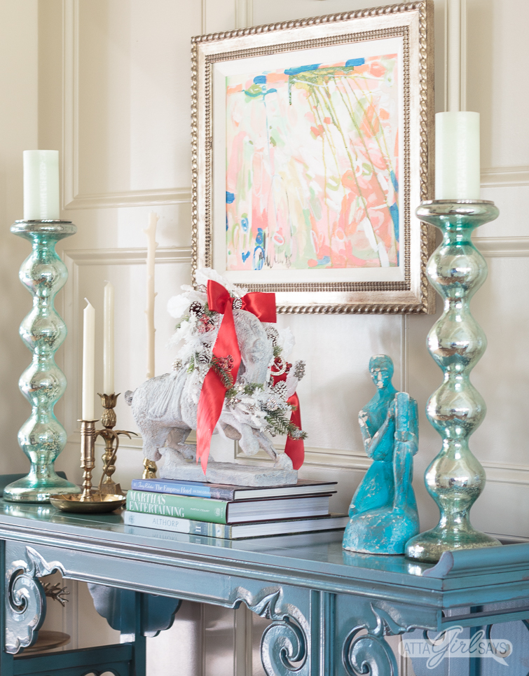 blue chinese style table decorated with books, a horse statue wearing a holiday wreath, and abstract art