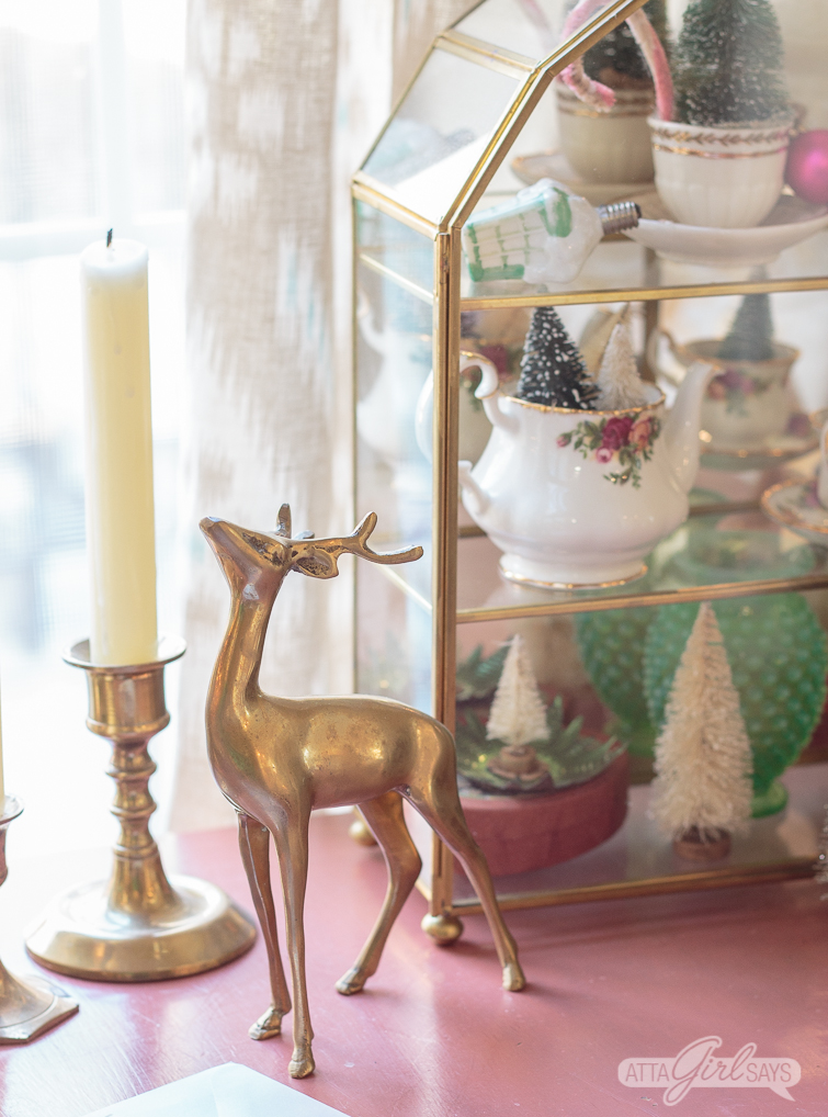 brass deer and candlesticks and brass shadowbox on a pink table