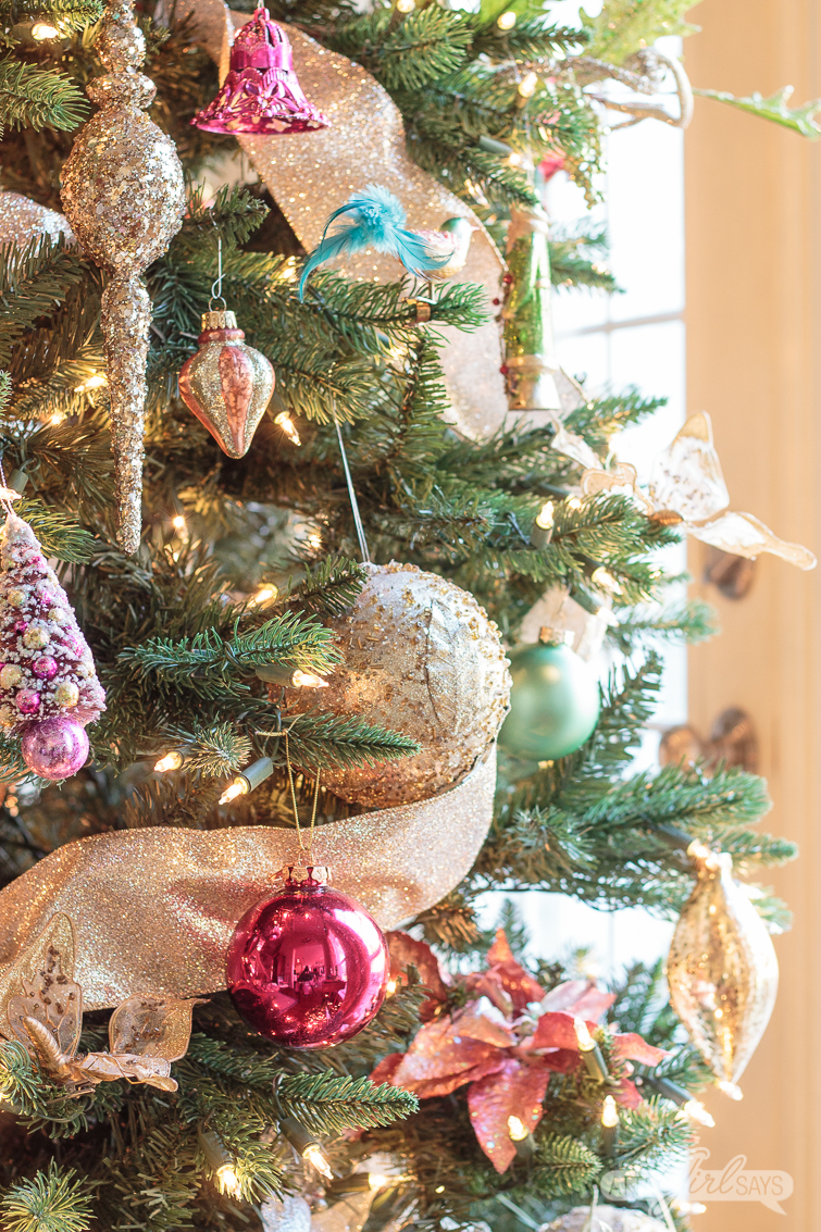 pink, green and gold ornaments on a Christmas tree decorated with gold ribbon