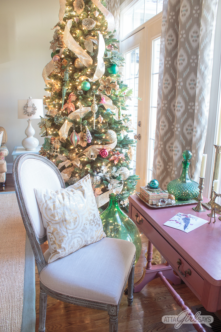 pink writing desk with green accessories and a beautiful Christmas tree in the background