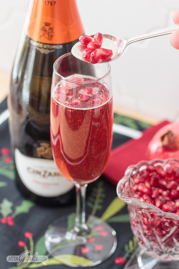 adding pomegranate seeds to a pomegranate mimosa