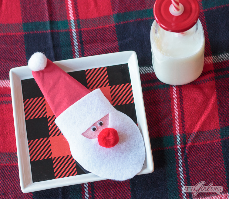 Felt Santa Claus Christmas napkin rings on a buffalo plaid square plate beside a glass bottle of milk