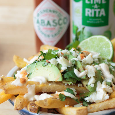 loaded french fries topped with avocado slices, cilantro and queso fresco cheese