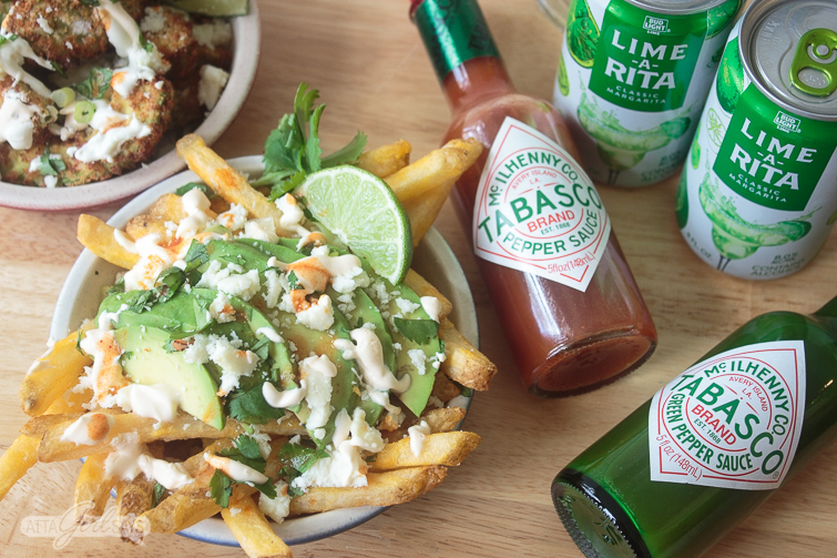 two types of loaded fries -- avocado fries and french fries topped with avocado slices