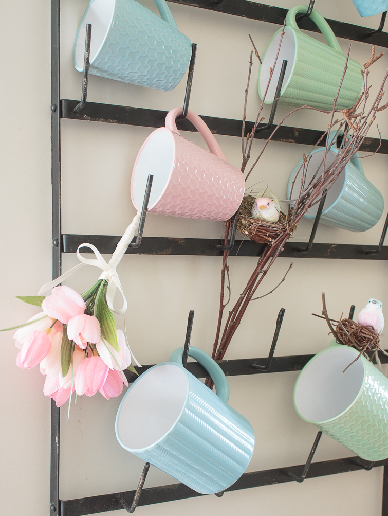 coffee mug rack decorated with pastel mugs and spring flowers and birds' nests