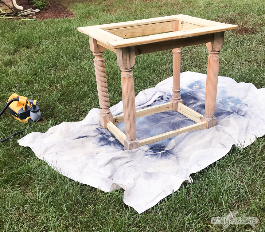 preparing to paint a wooden outdoor sink base with a Wagner paint sprayer