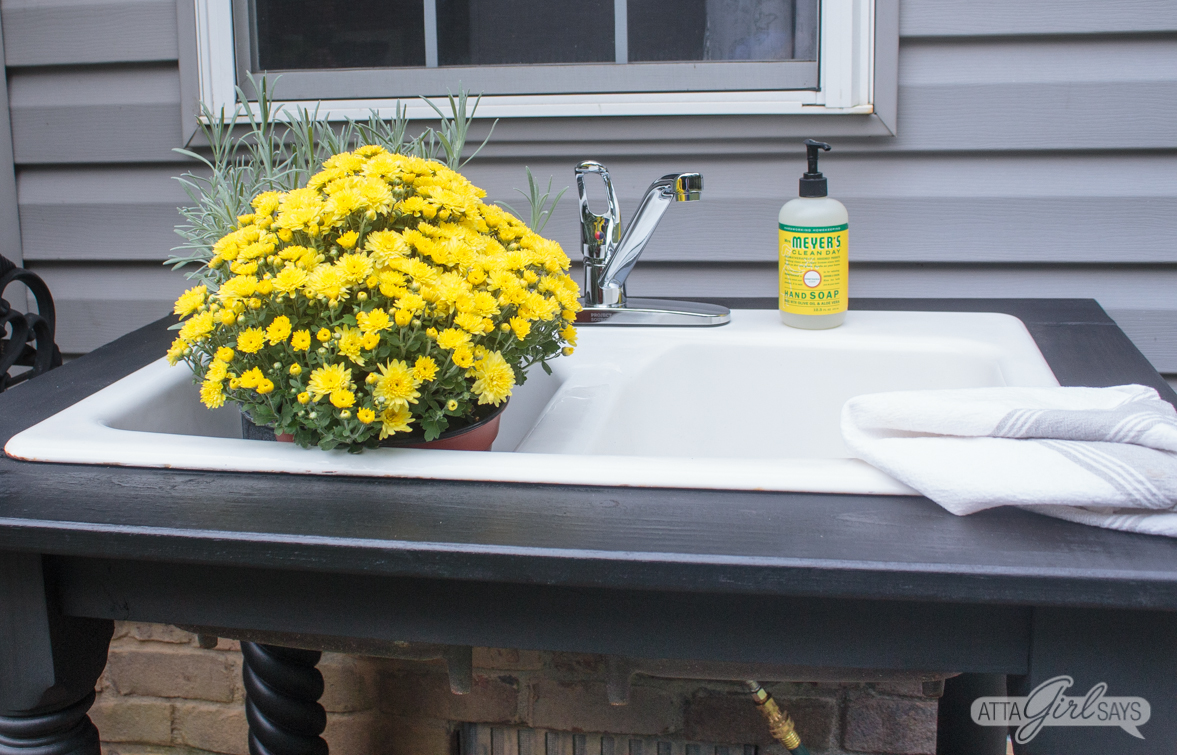 yellow mums in a white farmhouse outdoor sink
