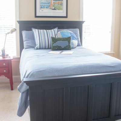 tween bedroom with black Pottery Barn style bed and blue comforter