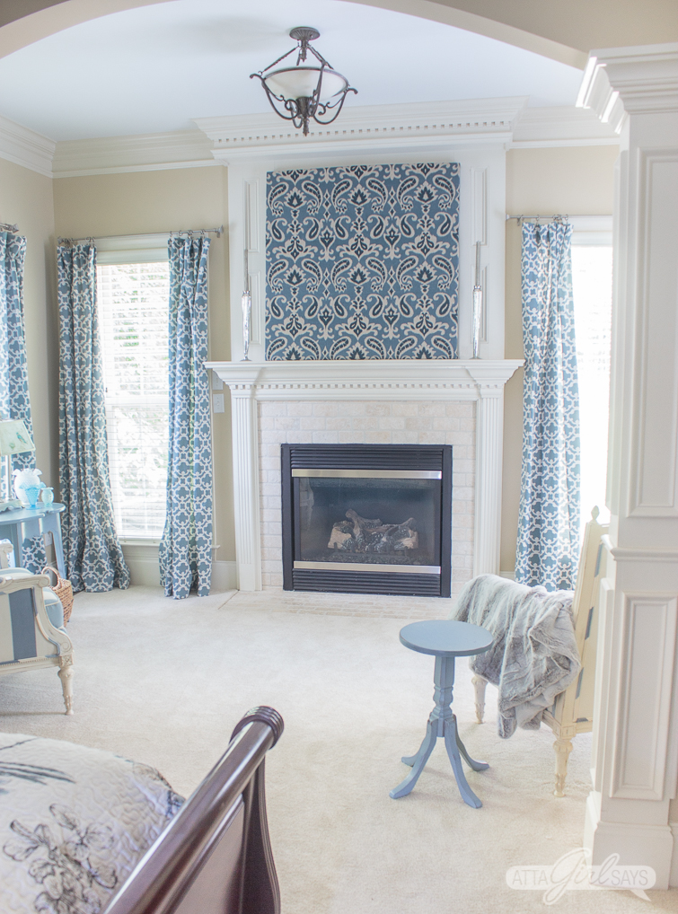 master bedroom sitting area with blue curtains and a fireplace with blue ikat artwork to hide a TV over a fieplace