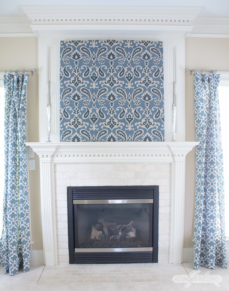 gas fireplace between two windows with blue ikat canvas artwork hanging above it