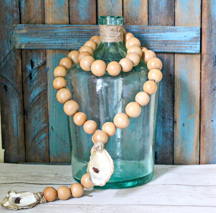 wooden beads with an oyster shell draped on a blue demijohn