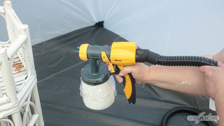 using a paint sprayer to paint a bamboo plant stand