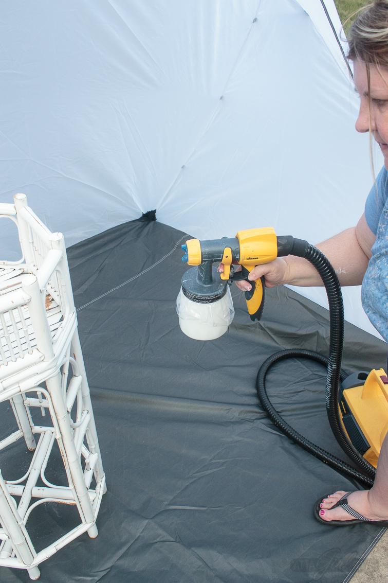 woman painting bamboo furniture with a paint sprayer