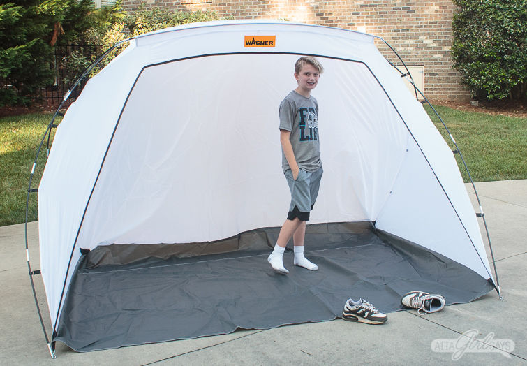boy standing in a spray painting tent shelter
