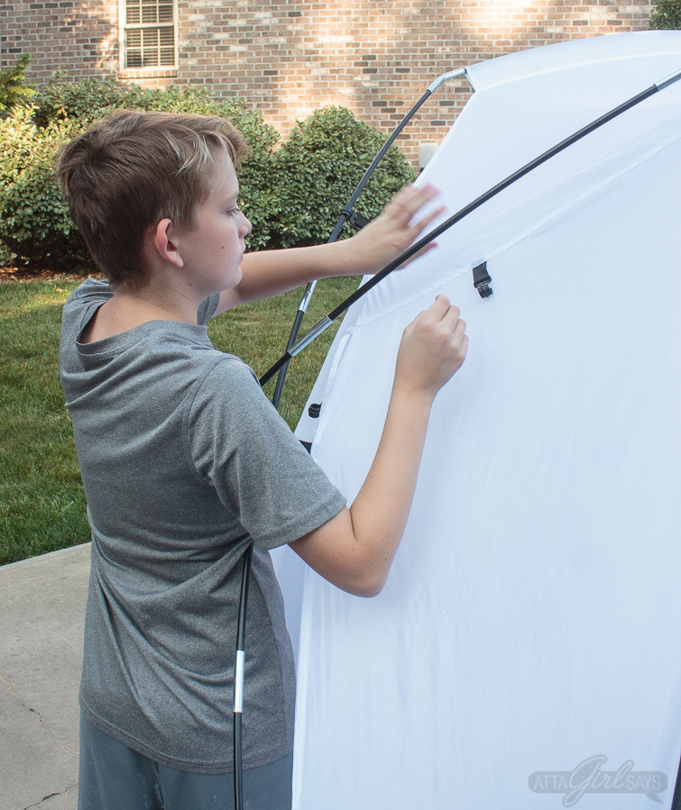 boy putting up a spray shelter tent