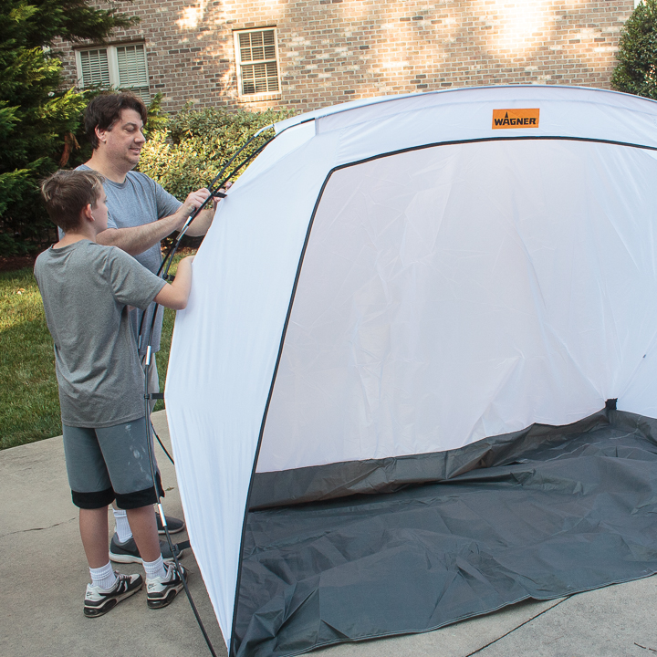 father and son putting up a spray shelter tent