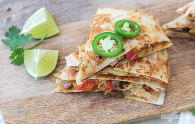 veggie quesadilla cut in wedges and topped with sliced jalapenos on a wooden board