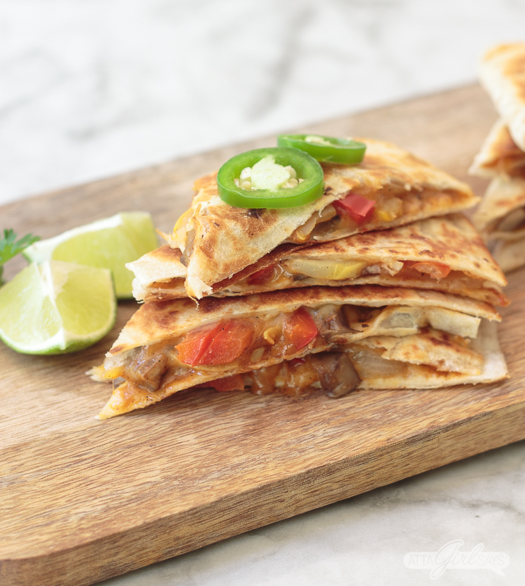stack of veggie fajitas, topped with jalapeno slices, on a wooden board