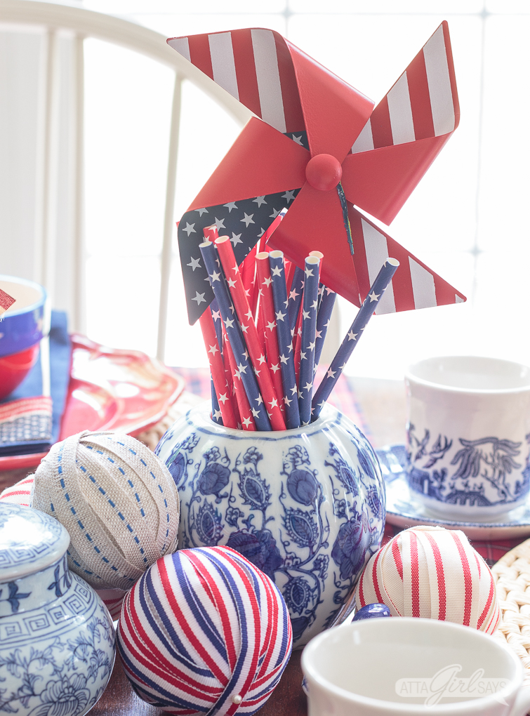 ribbon wrapped balls and a blue and white jar filled with paper straws on a patriotic 4th of July tablescape