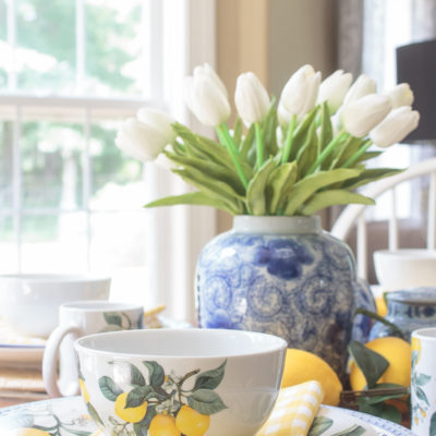 yellow lemon bowl on a dining table with a blue and white vase of tulips in the background
