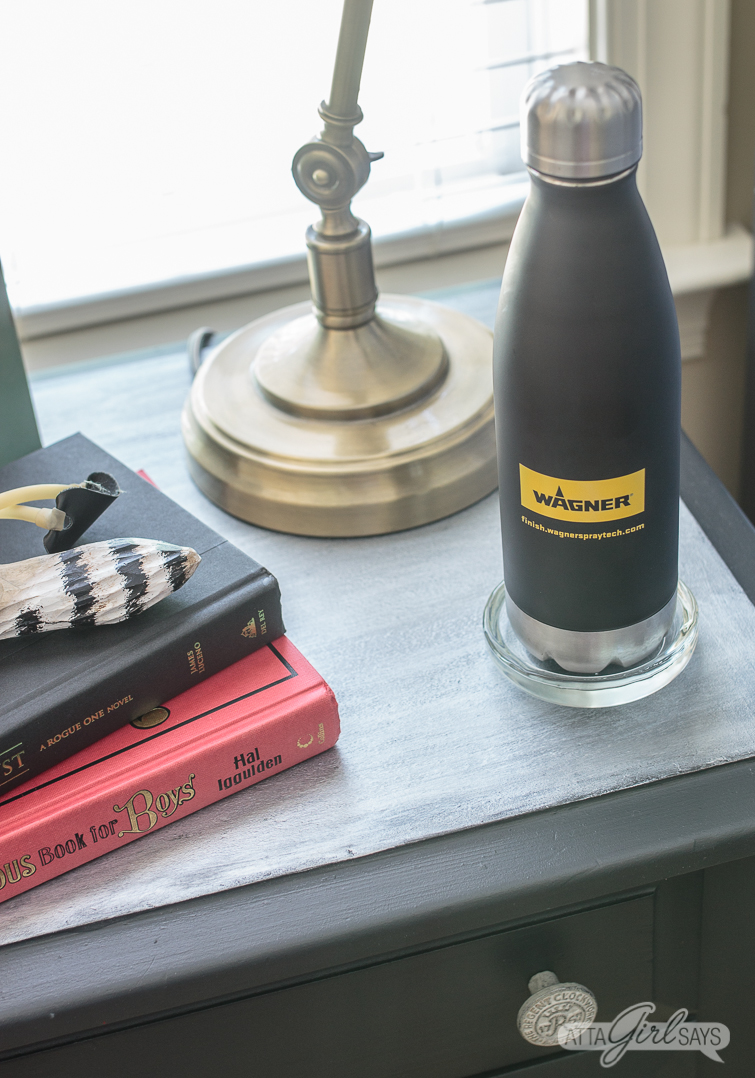 metallic nightstand with books, a lamp and a metal water bottle sitting on it