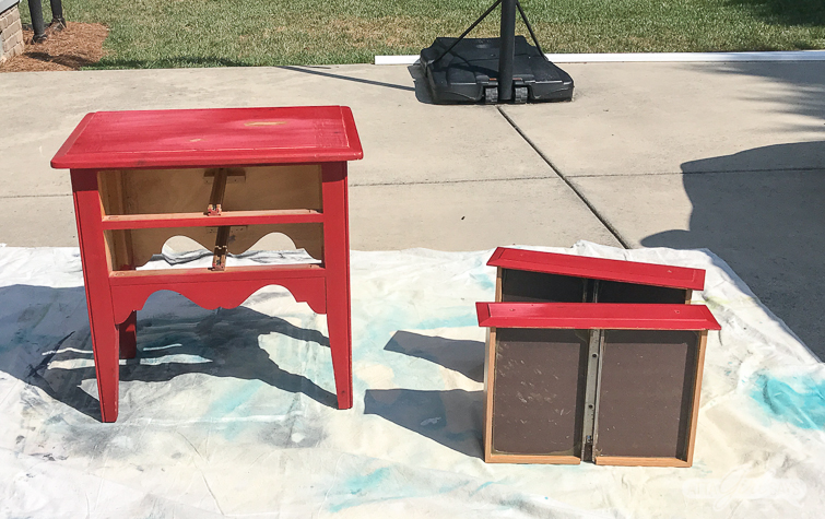 red nightstand with two drawers on a dropcloth