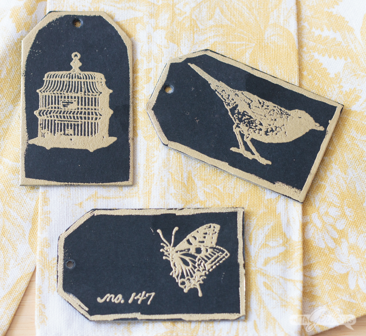 black cardstock tags with gold embossed bird, butterfly and birdcage images on them