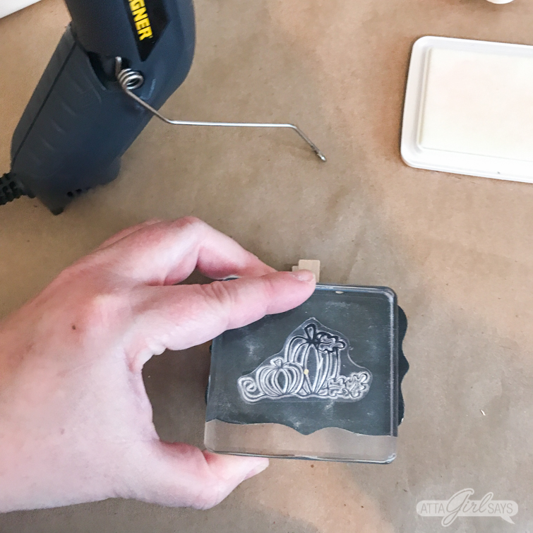stamping a pumpkin design with embossing ink on a chalkboard clip