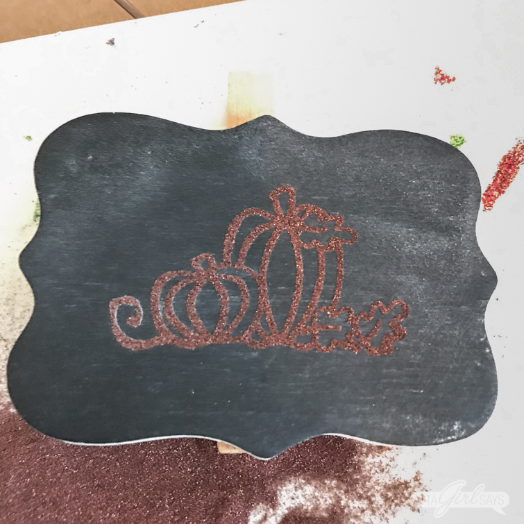 embossing powder over a stamped pumpkin design on a chalkboard clip