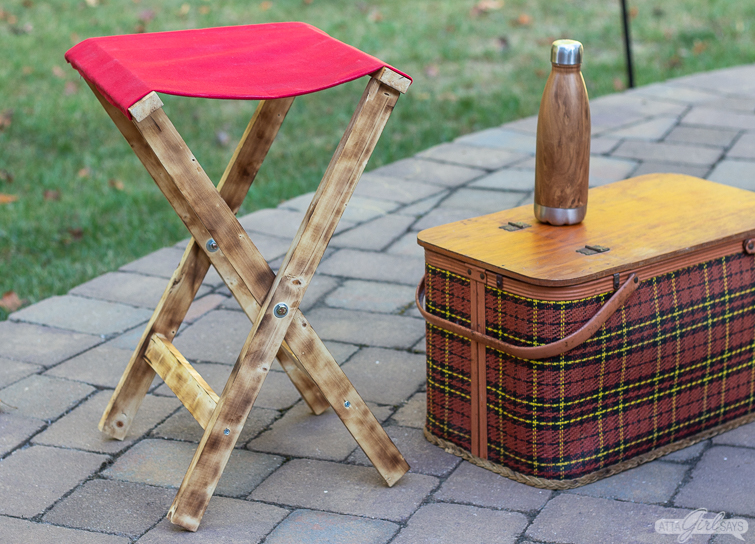 folding camp stool beside a plaid picnic basket