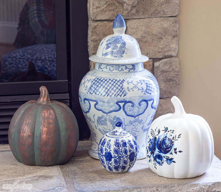 blue and white chinoiserie porcelain with copper and blue and white pumpkins on a stone hearth