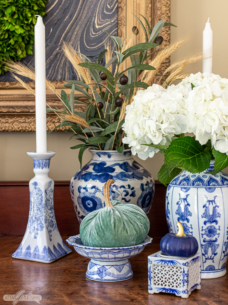 aqua velvet pumpkin on a pedestal alongside other blue and white chinoiserie pottery